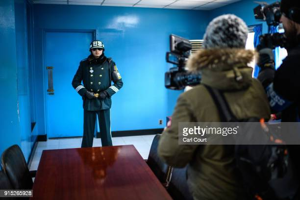 Members of the media film a South Korean soldier as he stands guard inside a Joint Security Area conference room at the border village of Panmunjom...