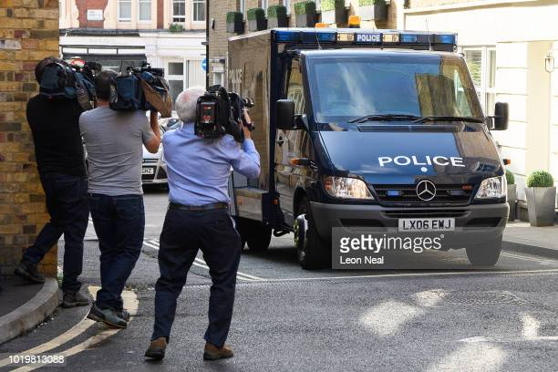 A photographer raises his camera to photograph inside an armoured vehicle at Westminster Magistrates court on the day that Salih Khater appears on...