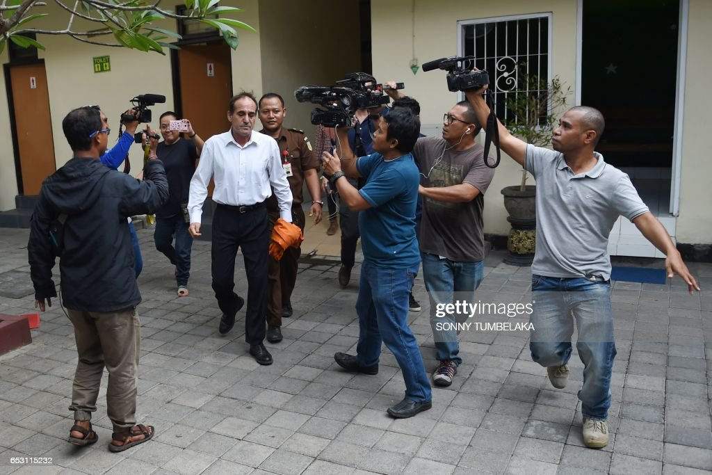 Members of the media follow Australian businessman Giuseppe Serafino (C) as he walks to a holding cell after his trial at a court in Denpasar on Indonesia's resort island of Bali on March 14, 2017. Serafino is charged with using, possessing and transporting hashish after allegedly being caught in possession of small amounts of the drug in October 2016. / AFP PHOTO / Sonny TUMBELAKA