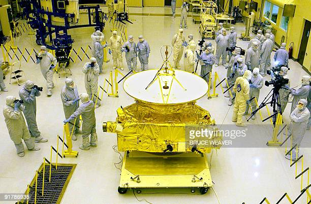 Members of the media garbed in protective unforms view NASA's New Horizons spacecraft 04 November 2005 in the Payload Hazardous Servicing Facility at...