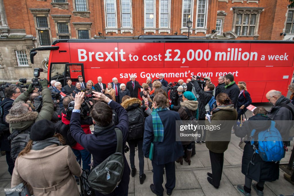 Members of the media gather around a bus with the campaign motto: 'Brexit to cost £2,000 million a week saysgovernment's own report. Is it worth it?' during its inauguration in London, U.K., on Wednesday, Feb. 21, 2018. With talk of a second referendum in the air, opponents of Brexit have decided to take their own red bus on the road. Photographer: Chris J. Ratcliffe/Bloomberg via Getty Images