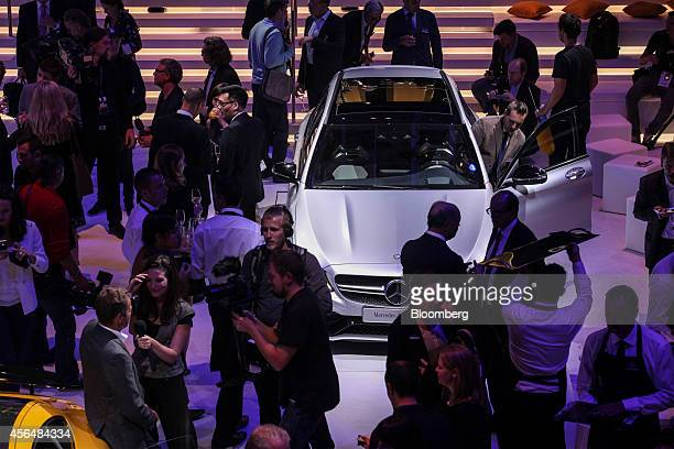 Members of the media gather around a MercedesAMG C63 automobile following a presentation at the MercedesBenz AG media night at the Piscine Molitor...