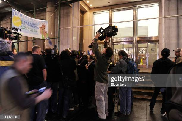 Members of the media gather in front of a building where they believe former International Monetary Fund Managing Director Dominique StraussKahn is...