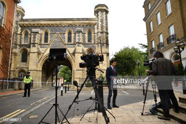Members of the media gather outside a police cordon, set up at the Abbey Gateway near Forbury Gardens park in Reading, west of London, on June 21,...