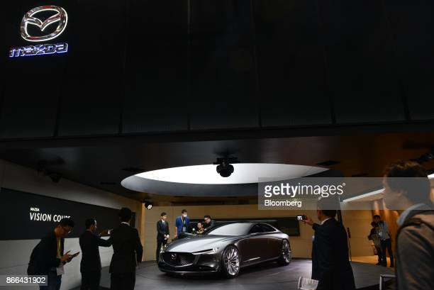 Members of the media look at a Mazda Motor Corp Vision Coupe concept vehicle at the Tokyo Motor Show in Tokyo Japan on Wednesday Oct 25 2017 Japan's...