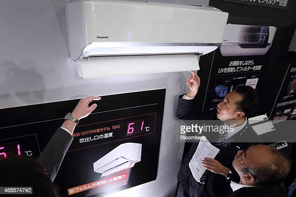 Members of the media look at Panasonic Corp's J Concept branded X series room air conditioner at an unveiling in Tokyo Japan on Wednesday Sept 17...