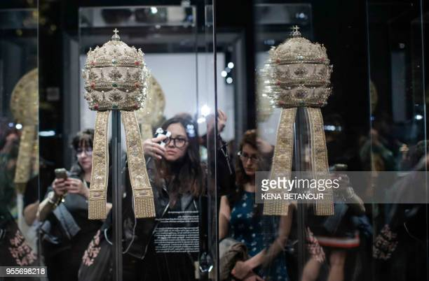Members of the media look at Papal Tiaras from the Sistine Chapel during the press preview for the annual fashion exhibit Heavenly Bodies Fashion and...