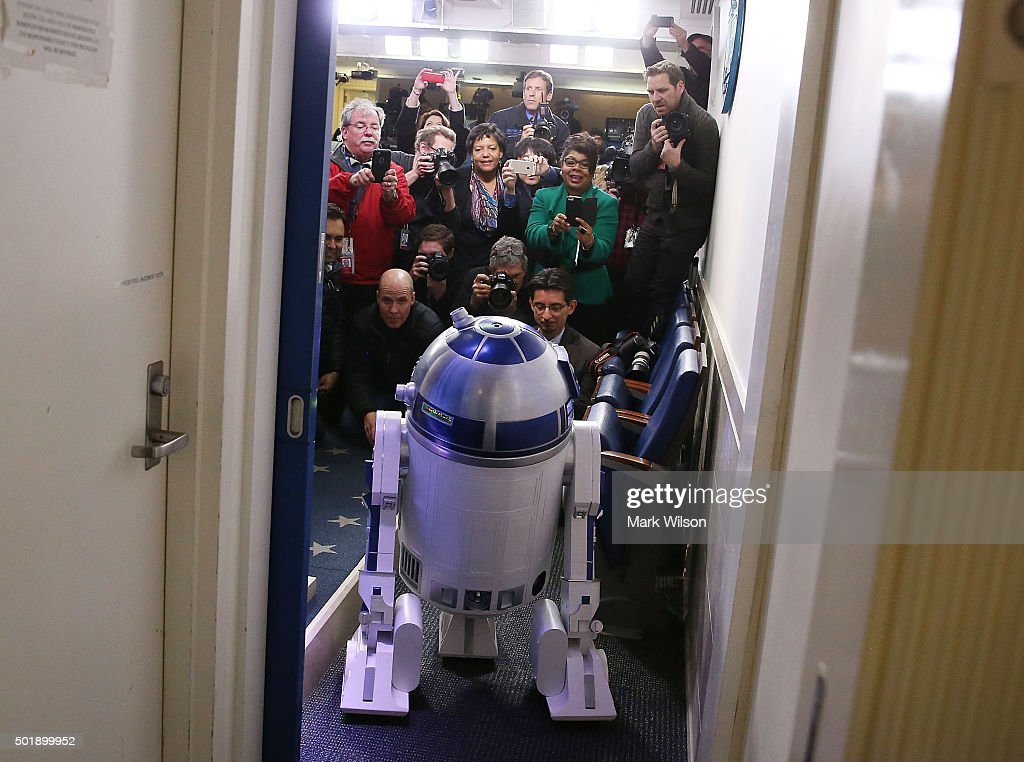 Members of the media look at Star Wars character R2-D2 as it visits the Brady Briefing Room at the White House December 18, 2015 in Washington, DC. The new Star Wars movie 'The Force Awakens' was shown at the White House for children of military families. U.S. President Barack Obama held his end of year press conference earlier today.