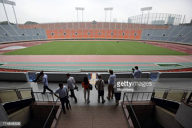Members of the media look at the existing National Olympic Stadium built for the 1964 Olympic games which will be demolished to make way for a new...