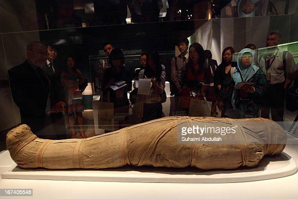 Members of the media look at the Mummy of Shepenmehyt exhibit during a media preview of the Mummy Secrets of the Tomb exhibition at ArtScience Museum...