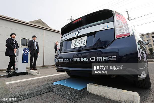 Members of the media observe a Toyota Motor Corp Prius PHV plugin hybrid vehicle reversing to park over the company's wireless vehicle charging...