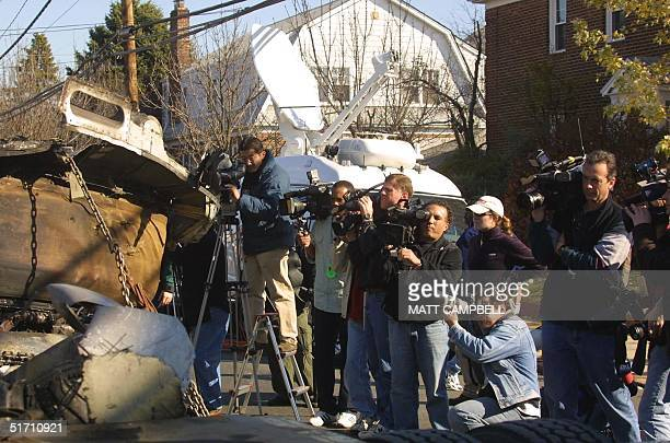 Members of the media photograph a piece of the engine from America Airlines Flight 587 after it was loaded into a truck 14 November, 2001 in the...