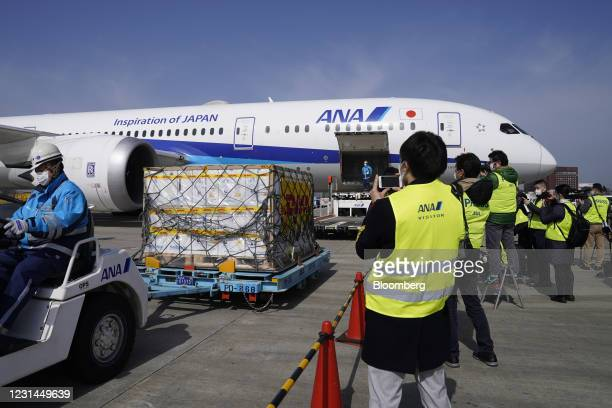Members of the media photograph and record video footage refrigerated containers carrying the Pfizer-BioNTech Covid-19 vaccine being unloaded from an...