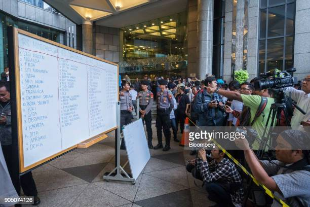 Members of the media photograph names of the injured victims sent to hospitals displayed on a whiteboard outside the Indonesia Stock Exchange complex...