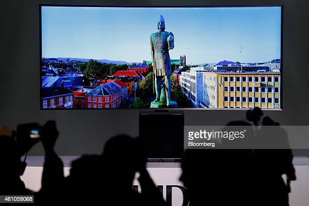 Members of the media photograph the Samsung Electronics Co SUHD 4K television during the 2015 Consumer Electronics Show in Las Vegas Nevada US on...