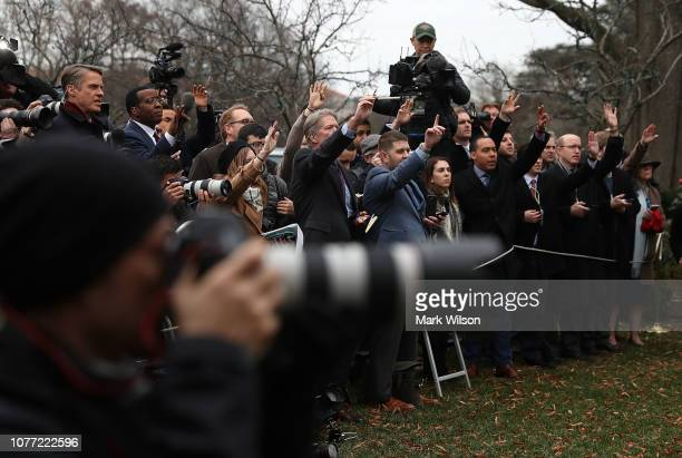 Members of the media raise their hands hoping to ask a question to US President Donald Trump after he attended a meeting with Congressional leaders...