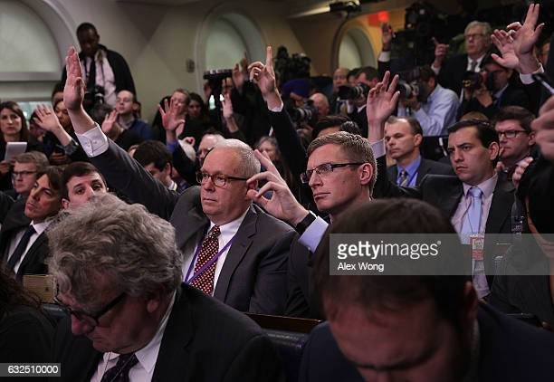 Members of the media raise their hands to ask questions during a daily briefing conducted by White House Press Secretary Sean Spicer at the James...