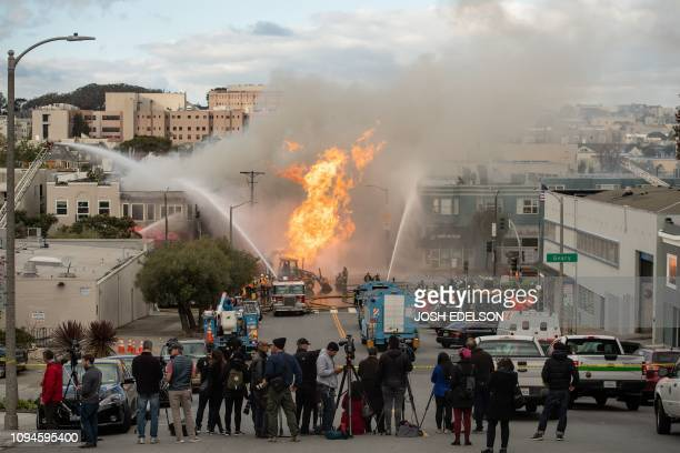 Members of the media record the scene as firefighters work to extinguish flames as they shoot into the air at an intersection in San Francisco...