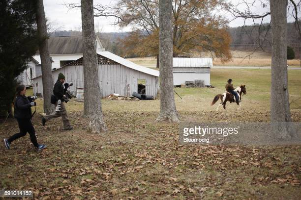 Members of the media run after Roy Moore Republican candidate for US Senate from Alabama as he departs on horseback from a polling location in...