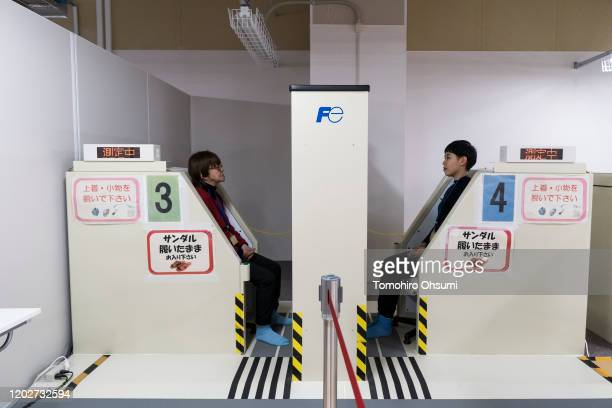 Members of the media sit in whole body counters at Tokyo Electric Power Co.'s Fukushima Dai-ichi nuclear power plant on January 29, 2020 in Okuma,...