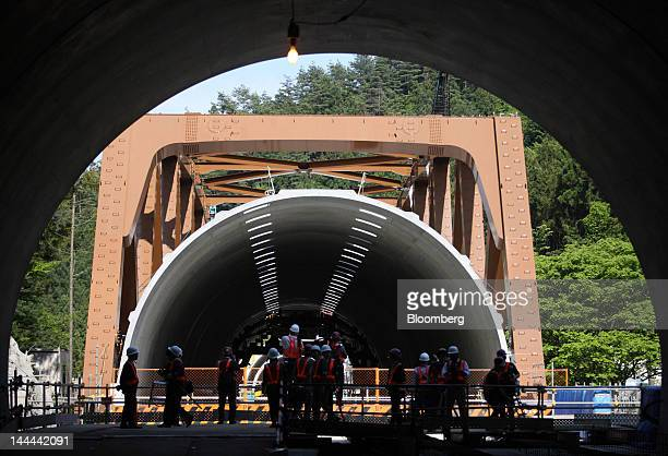 Members of the media stand at the entrance to the Akiyama tunnel which is under construction for Central Japan Railway Co's magneticlevitation train...