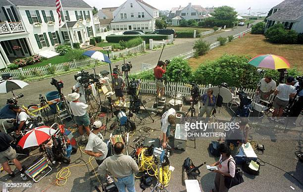 Members of the media stand by the entrance on the road leading to the Kennedy family compound in Hyannisport Massachusetts 19 July 1999 where family...