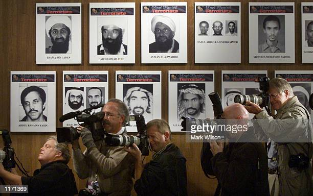 Members of the media stand next to a wall of the Most Wanted terrorists as US President George W Bush announces a new list of the FBI's Most Wanted...