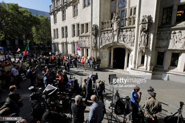 Members of the media stand opposite the entrance to the Supreme Court in central London on the first day of the hearing into the decision by the...