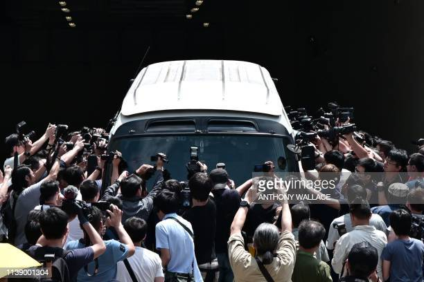 TOPSHOT Members of the media surround a prison van as it transports prominent leaders of the democracy movement from the West Kowloon Magistrates...