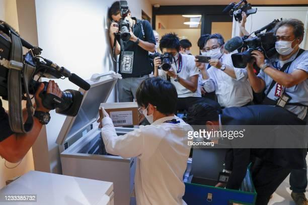 Members of the media surround staff members handling the Moderna Inc. Covid-19 vaccine during SoftBank Group Corp.'s coronavirus vaccination...
