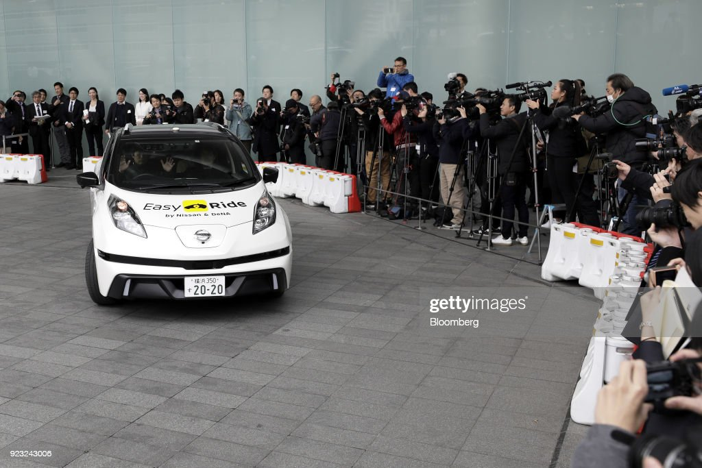 Members of the media take photographs and film a Nissan Motor Co. Leaf electric operated by the 'Easy Ride' robot taxi service, a joint development between Nissan and DeNA Co., during a demonstration in Yokohama, Japan, on Friday, Feb. 23, 2018. The service, which allows the public to use a smartphone app to book 15-minute rides, is scheduled to launch on March 5 for two weeks in Yokohama. Photographer: Kiyoshi Ota/Bloomberg via Getty Images