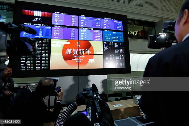 Members of the media take photographs and film video of the current figures of the Nikkei 225 Stock Average top right and the Topix Index top second...