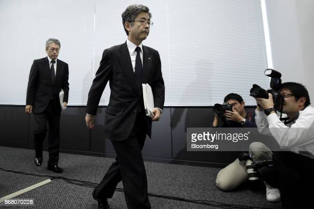 Members of the media take photographs as Naoto Umehara executive vice president of Kobe Steel Ltd center leaves a news conference in Tokyo Japan on...