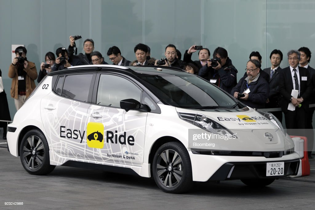 Members of the media take photographs of a Nissan Motor Co. Leaf electric operated by the 'Easy Ride' robot taxi service, a joint development between Nissan and DeNA Co., during a demonstration in Yokohama, Japan, on Friday, Feb. 23, 2018. The service, which allows the public to use a smartphone app to book 15-minute rides, is scheduled to launch on March 5 for two weeks in Yokohama. Photographer: Kiyoshi Ota/Bloomberg via Getty Images