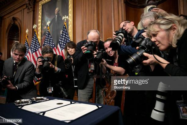 Members of the media take photographs of the articles of impeachment ahead of an engrossment ceremony in Washington, D.C., U.S., on Wednesday, Jan....