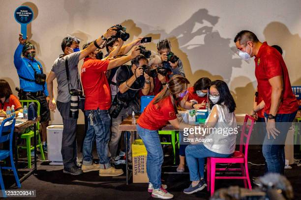 Members of the media take pictures as a healthcare worker administers a dose of Sinovac Biotech's CoronaVac vaccine to a woman at a mall theatre...