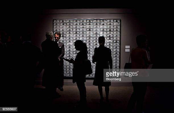 Members of the media talk near look over '200 One Dollar Bills' by Andy Warhol during a preview of the Contemporary Art fall sale at Sotheby's in New...