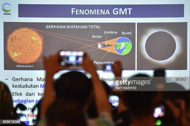 Members of the media try to get photos at a press briefing by the Indonesian Agency for Meteorological Climatological and Geophysics about the...
