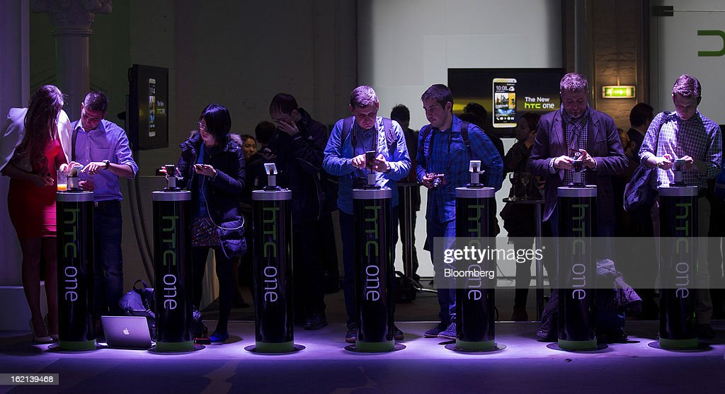 Members of the media view the new HTC One smartphone during a launch event in London, U.K., on Tuesday, Feb. 19, 2013. HTC Corp. introduced its new flagship HTC One smartphone at a launch event in London today. Photographer: Simon Dawson/Bloomberg via Getty Images