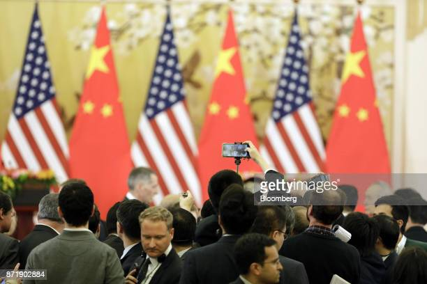 Members of the media wait for US President Donald Trump and China's president Xi Jinping to arrive for a news conference at the Great Hall of the...