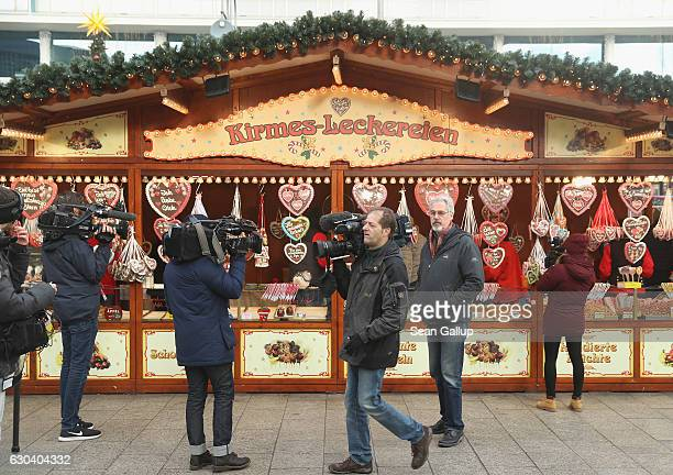 Members of the media walk past gingerbread hanging at a food stand that reopened moments before at the Breitscheidplatz Christmas market only a short...