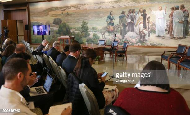 Members of the media watch as Russell M Nelson speaks via television from the historic Mormon Salt Lake Temple too members of the Church of Jesus...