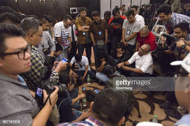 Members of the media watch live broadcasts of the swearing in ceremony of Mahathir Mohamad Malaysia's prime minister on smartphones ahead of a news...