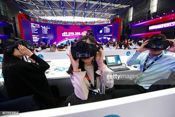 Members of the media wear virtual reality headsets and experience Alibaba's VR shopping technology Buy at Shenzhen Universiade Sports Centre during...