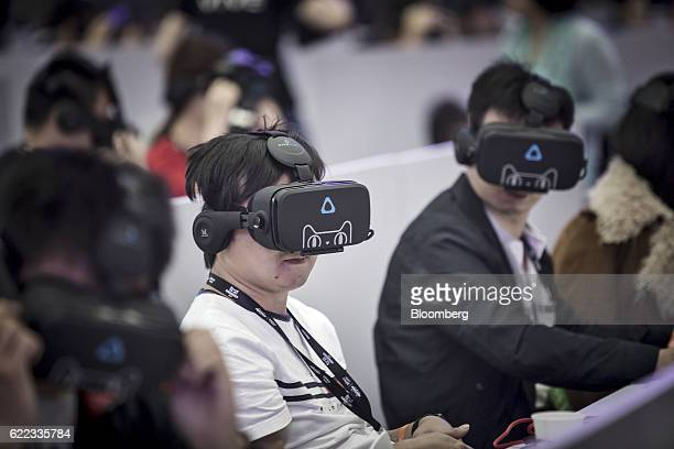 Members of the media wear virtual reality headsets featuring the Tmall Cat mascot for Alibaba Group Holding Ltd's Tmall online marketplace at...