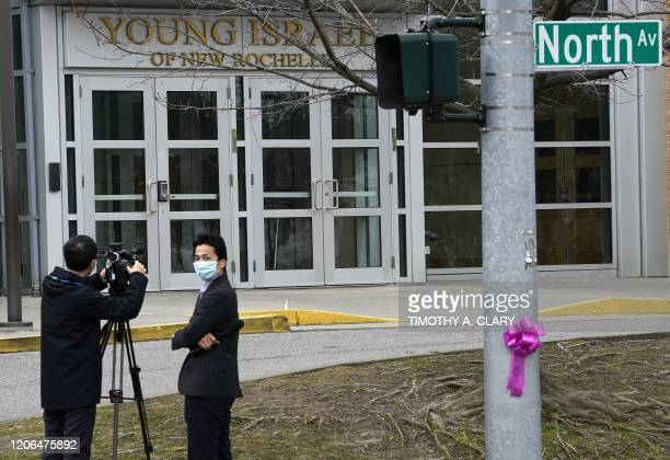 Members of the media wearing protective mask film outside the Young Israel of New Rochelle synagogue New York on March 10 at the center of a...