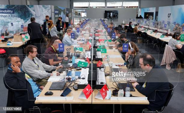 Members of the media work at desks screened-off due to Covid-19, in the media centre at Falmouth, Cornwall on June 10 ahead of the three-day G7...