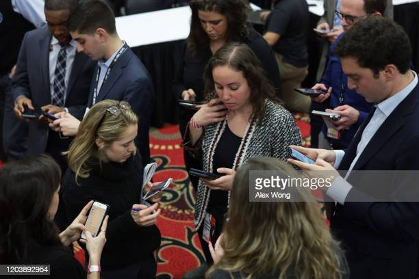 Members of the media work on their phones as they wait for the results during a caucus night event of Democratic president candidate Sen Bernie...