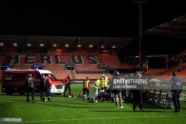 Members of the medical staff and firemen try to rescue a man in critical conditions, who's lying on the football picth after he was hit by the fall...