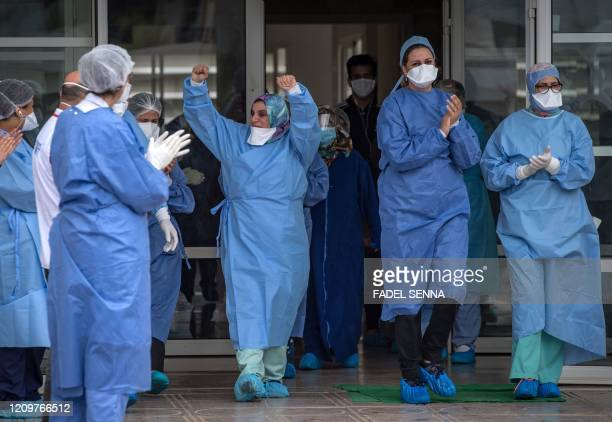 Members of the medical staff rejoice as patients who recovered from the Covid-19 disease caused by the novel coronavirus , leave a hospital in the...